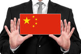 Businessman holding a business card with China Flag — Stock fotografie