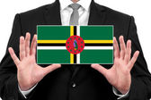 Businessman holding a business card with Dominica Flag — Stock fotografie