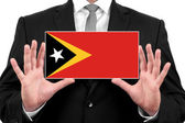 Businessman holding a business card with East Timor Flag — Stock Photo