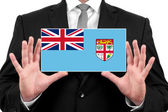 Businessman holding a business card with Fiji Flag — Foto de Stock
