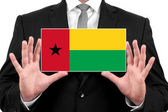 Businessman holding a business card with Guinea Bissau Flag — Stock Photo