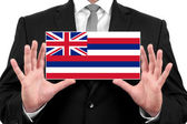 Businessman holding a business card with Hawaii Flag — Stock fotografie