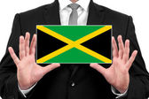Businessman holding a business card with Jamaica Flag — Stock Photo