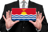 Businessman holding a business card with Kiribati Flag — Foto de Stock