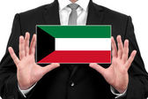 Businessman holding a business card with Kuwait Flag — Stock Photo