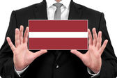 Businessman holding a business card with Latvia Flag — Stock Photo