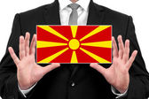 Businessman holding a business card with Macedonia Flag — Foto de Stock