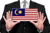 Businessman holding a business card with Malaysia Flag — Stock Photo