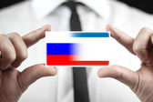 Businessman holding a business card with Autonomous Republic of Crimea and Russia Flag — Stock Photo