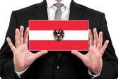Imprenditore in possesso di un biglietto da visita con bandiera austria — Foto Stock