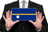 Businessman holding a business card with Nauru Flag — Stock Photo