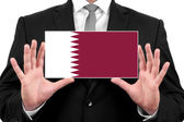 Businessman holding a business card with Qatar Flag — Stock Photo