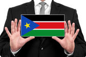 Businessman holding a business card with South Sudan Flag — Stock Photo