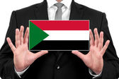 Businessman holding a business card with Sudan Flag — Stock Photo