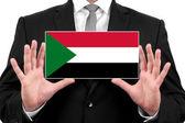 Empresário segurando um cartão com a bandeira do sudão — Foto Stock