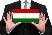 Businessman holding a business card with Tajikistan Flag — Foto de Stock