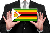 Businessman holding a business card with Zimbabwe Flag — Zdjęcie stockowe