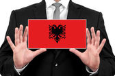 Businessman holding a business card with Albania Flag — Stock Photo
