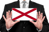 Businessman holding a business card with Alabama State Flag — Stock Photo