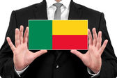 Businessman holding a business card with Benin Flag — Stock Photo