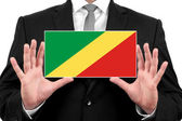 Businessman holding a business card with Congo Republic Flag — Stock Photo