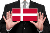 Businessman holding a business card with Denmark Flag — Stock Photo