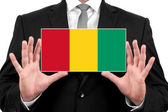 Businessman holding a business card with Guinea Flag — Stock Photo