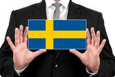 Businessman holding a business card with Sweden Flag — Stock Photo