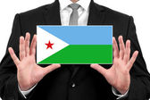 Businessman holding a business card with Djibouti Flag — Stock Photo