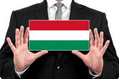 Businessman holding a business card with Hungary Flag — Stock Photo