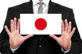 Businessman holding a business card with Japan Flag — Stock Photo
