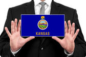 Businessman holding a business card with Kansas State Flag — Stock Photo