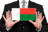 Businessman holding a business card with Madagascar Flag — Stock Photo