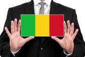 Businessman holding a business card with Mali Flag — Stock Photo