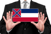 Businessman holding a business card with Mississippi State Flag — Stock Photo