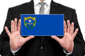 Businessman holding a business card with Nevada State Flag — Stock Photo