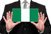 Businessman holding a business card with Nigeria Flag — Stock Photo