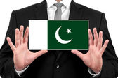 Businessman holding a business card with Pakistan Flag — Stock Photo