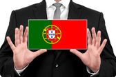 Businessman holding a business card with Portugal Flag — Stock Photo