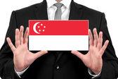 Biznesmen posiadania wizytówki z flaga singapuru — Zdjęcie stockowe
