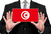 Businessman holding a business card with Tunisia Flag — Stock Photo