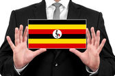 Businessman holding a business card with Uganda Flag — Stock Photo