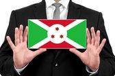 Businessman holding a business card with Burundi Flag — Stock Photo