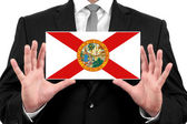 Businessman holding a business card with Florida State Flag — Stock Photo