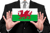 Businessman holding a business card with Wales Flag — Stock Photo