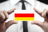 Businessman holding a business card with South Ossetia Flag — ストック写真