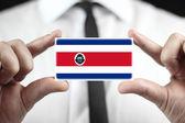 Biznesmen posiadania wizytówki z flaga kostaryki — Zdjęcie stockowe
