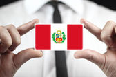 Businessman holding business card with Peru Flag — Stock Photo