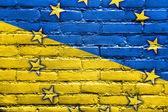 Tuğla duvara boyalı ukrayna ve avrupa birliği bayrağı — Stok fotoğraf