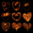 Flamy heart symbols on the black background - 图库照片